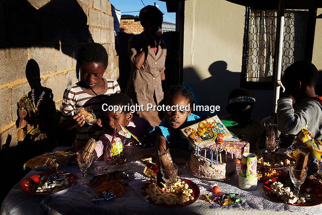 SOWETO, SOUTH AFRICA MAY 4: A children's birthday party outside a house on May 4, 2013 Orlando section Soweto, South Africa. Soweto today is a mix of old housing and newly constructed townhouses. A new hungry black middle-class is growing steadily. Many residents work in Johannesburg but the last years many shopping malls have been built, and people are starting to spend their money in Soweto. (Photo by: Per-Anders Pettersson)