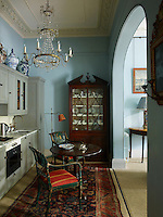 The kitchen has been furnished with antiques that lend a distinctive mood. Large oriental jars sit atop the cupboards and a crystal chandelier adds an elegant touch. The kitchen area opens onto the sitting room.