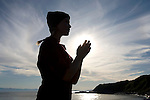 A young girl wearing a hat prays on a beach along Dallas Road in Victoria, BC, British Columbia, Canada.