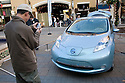 Man photographing new Nissan Leaf prototype. Nissan Leaf Zero Emission Tour promotional event for the Nissan Leaf electric car that is scheduled to be released in Fall 2010. Car specs from Nissan: 5 person capacity, 90 MPH top speed, lithium-ion battery, 100 mile average range per charge. Santana Row, San Jose, California, USA, 12/5/09