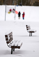 Snow covers the seats on benches as children and adult sled a small hill in a city park in Westerville, Ohio, after the first snowfall of the season.  Photo Copyright Gary Gardiner. Not for reproduction without written permission.