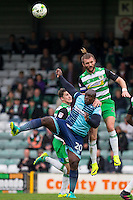 Darren Ward of Yeovil Town beats Adebayo Akinfenwa of Wycombe Wanderers in the air during the Sky Bet League 2 match between Yeovil Town and Wycombe Wanderers at Huish Park, Yeovil, England on 8 October 2016. Photo by Mark  Hawkins / PRiME Media Images.