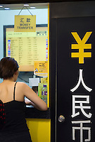 HONG KONG, MARCH 18: A person exchanges money at a currency exchange booth showing symbol of the Chinese yuan (RMB) and its name in Chinese characters, on March 18, 2015, in Hong Kong. (Photo by Lucas Schifres/Pictobank)