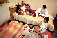 Somália settles into bed with six daughters while pregnant with a seventh. With only one bed and bedroom, the girls must sleep on a pile of blankets on the floor. The da Silvas keep the whole family in the room furthest from the street during the night for fear of frequent stray bullets and police raids on the slum.