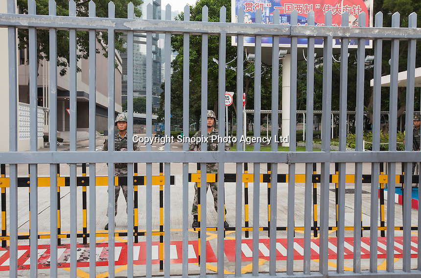 Chinese People's Liberation Army (PLA) soldiers stand on guard at their barracks on day three of the mass civil disobedience campaign Occupy Central, Hong Kong, China, 30 September 2014. Their is widespread fear in Hong Kong that the PLA will enforce a crackdown similar to the one that took place in Beijing's Tiananmen Square in 1989 killing many student protesters.
