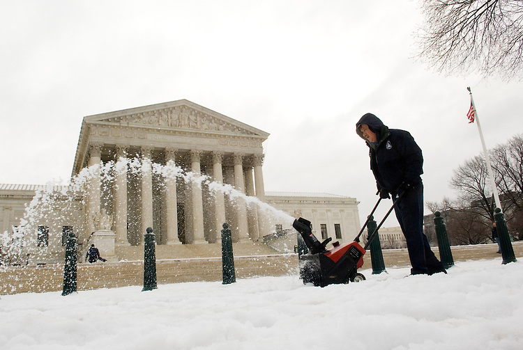 A worker with the Architect of the Capitol office uses a snow blower to clear the sidewalk in front of the Supreme Court on Wednesday morning, Feb. 14, 2007, following a winter storm that covered the Washington area with snow and ice.