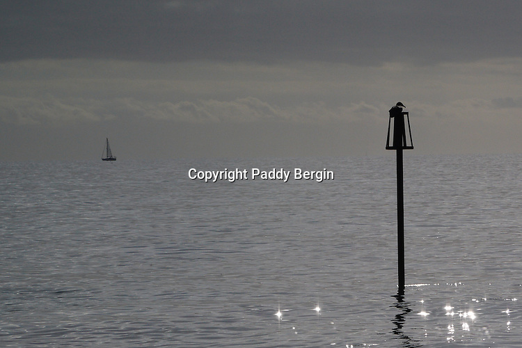 Sea View,outflow pipe,gull sitting on outflow pipe,view of yacht,light twinkling on water.<br />