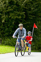 Rob  and Josh riding bike with tagalong attachment.  ..Virginia Water , Surrey  July 2004..