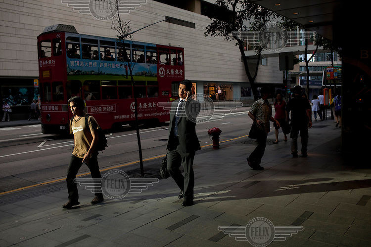 A man talks on his mobile phone in a commercial area of central Hong Kong.