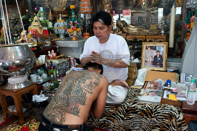 Tattoo master (Khru Sak) Ajarn Noo, who became Thailand's most famous tattooist after he tattooed film star Angelina Jolie, blesses a tattoo (Sak Yan or Sacred Tattoo) on the back of one of his luuk sit (disciples) .