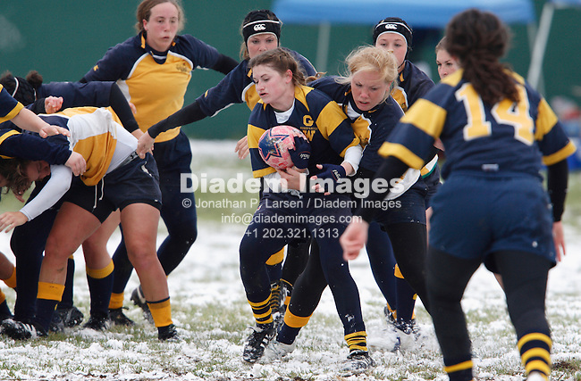 A George Washington University player is tackled by a Naval Academy opponent during a snowy women's match at the annual Cherry Blossom Rugby Tournament at Rosecroft Raceway in Fort Washington, Maryland.