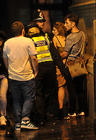 Pictured: Police officers speak to a young couple in the early hours of New Year's Day. Sunday 01 January 2017<br /> Re: Revellers out celebrating the New Year in the pub and club on Wind Street Swansea