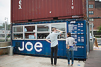 Customers peruse the menu at Joe, a coffee bar, in the Dekalb Market in downtown Brooklyn in New York, seen on Saturday, September 10, 2011.  The market, which uses decorated and modified shipping containers as kiosks for its vendors, is located in the high density area of downtown Brooklyn and includes vendors selling food, clothing and accessories, all from local sellers. The market is the product of Urban Space, which has over 20 container projects in London and produces temporary Christmas holiday markets in parks in New York.  (© Richard B. Levine)