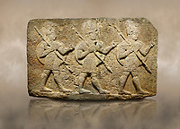 Photo of Hittite monumental relief sculpted orthostat stone panel of Herald's Wall Basalt, Karkamıs, (Kargamıs), Carchemish (Karkemish), 900-700 B.C. Anatolian Civilisations Museum, Ankara, Turkey. Military parade. Two helmeted soldiers in short skirts carry the shield on their backs and the spears in their hands. <br /> <br /> Against a brown art background.