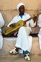 Merzouga, Morocco.  Gnaoua Musician Playing his Gimbrie, or Hajouj.