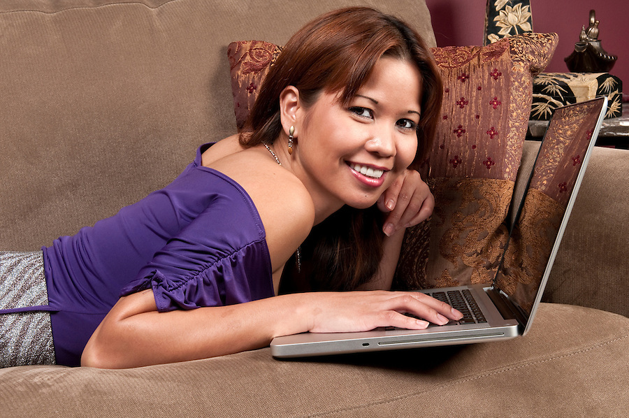 Young woman relaxing in the sofa and navigating in internet.