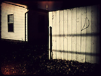 Fence and house in light at sunset. dark and moodyiPhone photo