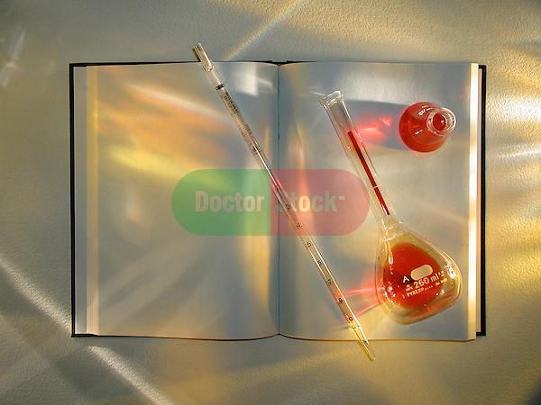 still-life of journal with medical glassware, pipette, flask