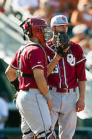 Oklahoma Sooners starting pitcher Dillon Overton #13 talks with catcher Anthony Hermelyn #9 in the eighth inning of the NCAA baseball game against the Texas Longhorns on April 6, 2013 at UFCU DischFalk Field in Austin, Texas. The Longhorns defeated the rival Sooners 1-0. (Andrew Woolley/Four Seam Images).