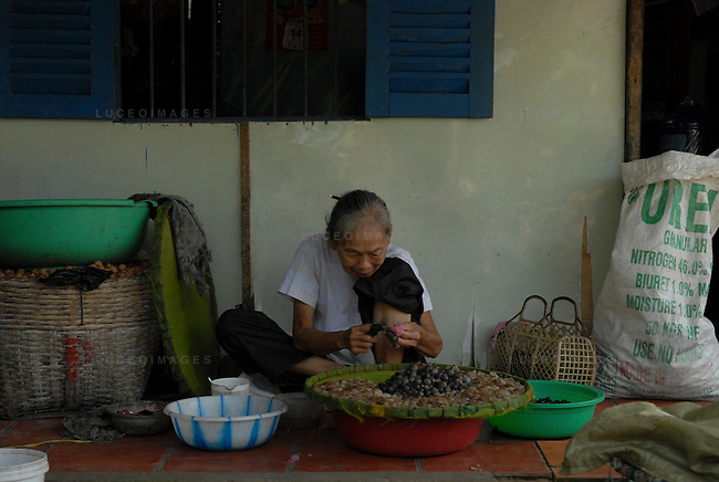 A woman peels shellfish along the Mekong River in Vietnam.