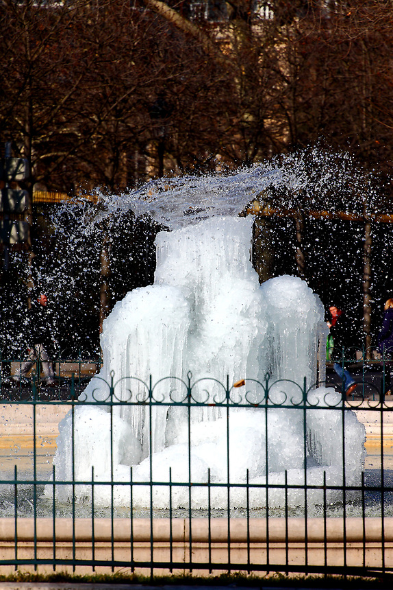 Paris Left Bank: The icy fountain of place Edmond Rostand, near the Luxembourg gardens, after the snow, with its beautiful spurt of water.