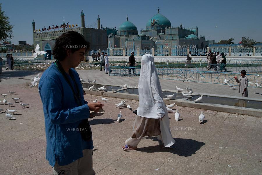 """AFGHANISTAN - MAZAR-E CHARIF - 7 aout 2009 : .Le nom de Mazar-e Charif signifie """"sanctuaire sacre"""" et fait reference au sanctuaire et a la mosquee qui auraient ete batis, selon les afghans chiites comme sunnites, sur le tombeau de l'imam Ali. Ancien lieu de culte paien puis boudhiste, le sanctuaire de Mazar-e Charif est aujourd'hui le plus grand centre de pelerinage musulman en Afghanistan. Son activite culmine a l'occasion du nouvel an afghan, le 21 mars de chaque annee...Delazad Deghati sur l'esplanade de la Mosquee. ..AFGHANISTAN - MAZAR-E CHARIF - August 7th, 2009 : The name Mazar-e Charif means """"sacred sanctuary"""" and refers to the sanctuary and mosque which were built, according to Sunni and Shiite Afghans alike, over the tomb of the Imam Ali. An ancient religious site for Pagans and then Buddhists, today the Mazar-e Charif sanctuary is the Muslim pilgrimage centre of Afghanistan. Activity here culminates annually on March 21, Afghan New Year..Delazad Deghati on the plaza of the mosque."""