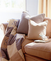 A patchwork throw and cushions on a sofa in preparation for a relaxing afternoon