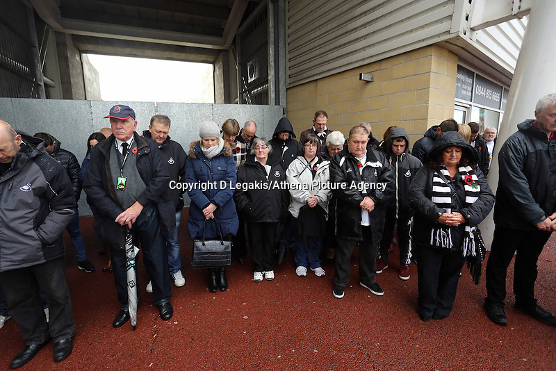 Sunday 09 November 2014<br /> Pictured: Swansea supporters observe a minute's silence after the plaque unveiling <br /> Re: Swansea City FC have unveiled a plaque for three former players who died during the First World War commemorating this way Remembrance Sunday. It was unveiled before the Barclays Premier League, Swansea City FC v Arsenal City at the Liberty Stadium, south Wales, UK