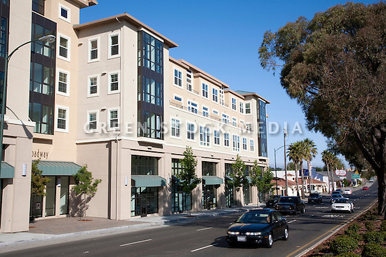Cars driving near a mixed use building. Park Broadway on El Camino Real in Millbrae, CA is a mixed use development featuring 96 residential condominiums and 13 ground floor live-work lofts for small business offices. The developer Silverstone Communities promotes energy efficient features such as dual-glazed low-emission windows, high-density thermal insulation, individual electric meters, HVAC systems for each unit, and energy-efficient heating systems. Park Broadway is walking distance to downtown amenities.