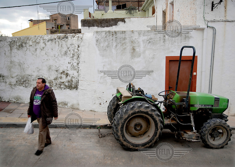A portrait of Alejandro Cao de Benos, photographed in the village of Salomo in northeast Spain walking past a tractor. As a Korean-Spanish communist, Alejandro is the president of the Korean Friendship Association (KFA) and has been an advocate of the Democratic People's Republic of Korea (North Korea) since 1990. His Korean name is Zo Sun-il (Korea is One) and he works as an honorary Special Delegate of the DPRK's Committee for Cultural Relations with Foreign Countries - a North Korean government spokesman in Europe.