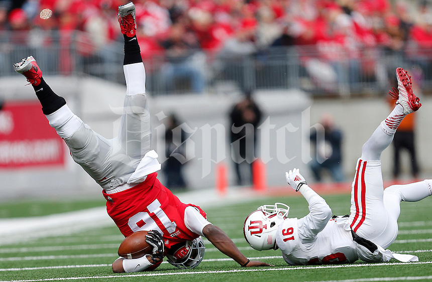 Ohio State Buckeyes quarterback J.T. Barrett (16) gets flipped through the air by Indiana Hoosiers cornerback Rashard Fant (16) in the first quarter of the college football game between the Ohio State Buckeyes and the Indiana Hoosiers at Ohio Stadium in Columbus, Saturday afternoon, November 22, 2014. As of half time the Ohio State Buckeyes led the Indiana Hoosiers 14 - 13. (The Columbus Dispatch / Eamon Queeney)
