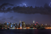Lightning bolts illuminate the night sky over the skyline of New York City during a summer thunderstorm.