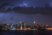 Lightning bolts illuminate the night sky over the skyline of New York City during a summer thunderstorm.