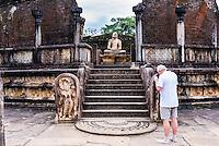 Ancient City of Polonnaruwa, tourist at the Vatadage (Circular Relic House) in Polonnaruwa Quadrangle, UNESCO World Heritage Site, Sri Lanka, Asia. This is a photo of a tourist at the Vatadage (Circular Relic House) in Polonnaruwa Quadrangle at the Ancient City of Polonnaruwa, a UNESCO World Heritage Site in Sri Lanka, Asia.
