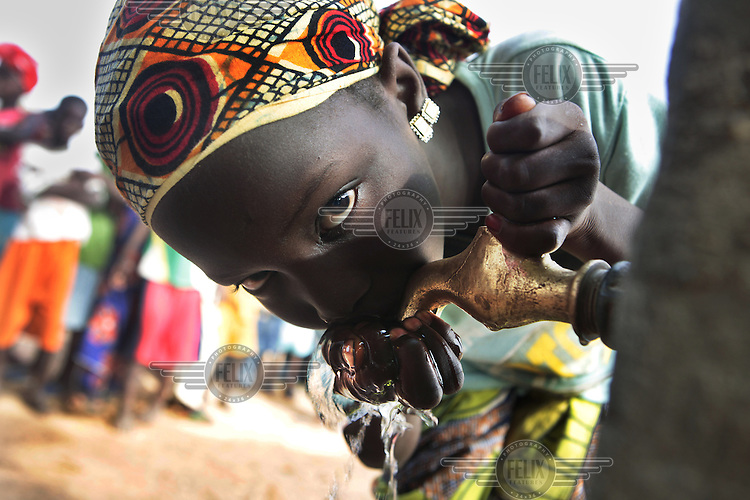 A girl drinks water from a tap at school. .