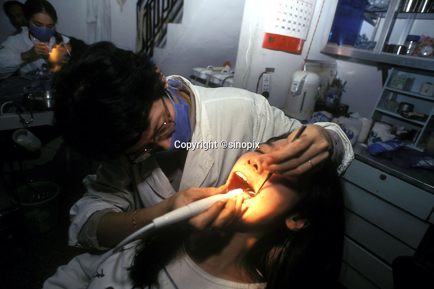 A woman has her teeth checked by a dentist in Fuzhou, China. Modern dental surgeons are now common in cities in China.