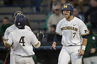 Michigan Wolverines catcher Harrison Wenson (7) greets teammate Ako Thomas (4) after scoring against the Michigan State Spartans during the NCAA baseball game on April 18, 2017 at Ray Fisher Stadium in Ann Arbor, Michigan. Michigan defeated Michigan State 12-4. (Andrew Woolley/Four Seam Images)
