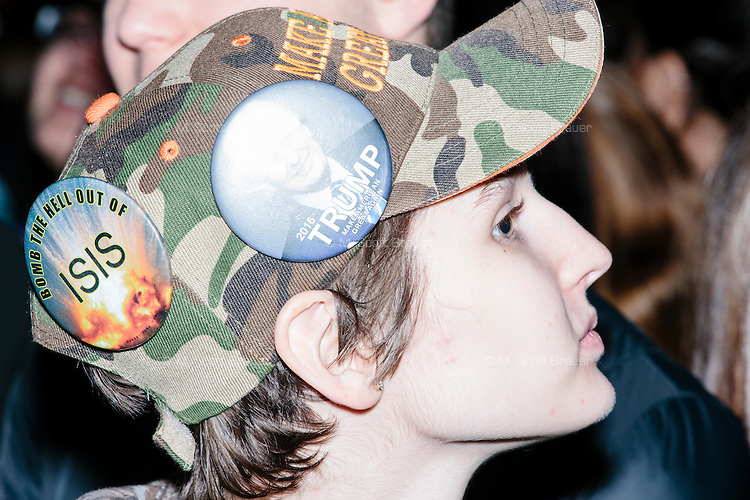 "A girl wears a camoflauge hat that says ""Make America Great Again"" and pro-Trump and anti-Hillary and -ISIS campaign buttons in the audience before real estate mogul and Republican presidential candidate Donald Trump speaks at a rally at Exeter Town Hall in Exeter, New Hampshire, on Thurs., Feb. 4, 2016."