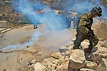 Israeli soldiers take cover after they succumb to the effects of their own CS gas grenade used in an attempt to disperse protesters during a demonstration against Israel's controversial separation barrier in the West Bank town of Beit Jala near Bethlehem on 04/07/2010.