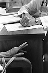 Vertical photo of doctor's hands taking notes, filling out paperwork on desk, with patient's hands gesturing in explanation
