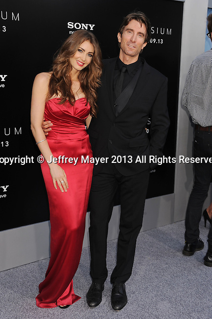 WESTWOOD, CA- AUGUST 07: Actor Sharlto Copley (R) and model Tanit Phoenix arrive at the Los Angeles premiere of 'Elysium' at Regency Village Theatre on August 7, 2013 in Westwood, California.