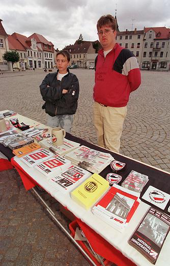 Vor allem mit Westkadern fuerte die rechtsextremistische NPD in Mecklenburg-Vorpommern einen sogenannten Schwerpunktwahlkampf zur Landtagswahlt 1998. Die Parteifuehrung rechnete sich in Mecklenburg-Vorpommern beste Chancen fuer Landtagsmandate aus. Sie blieb jedoch unter der Fuenf-Prozent-Huerde. Parteimitglieder gaben zu, da&szlig; es nur um die Wahlkampfkostenrueckerstattung ging.<br /> Hier: Wahlinformationsstand auf dem Marktplatz von Stavenhagen. Rechts, ein arbeitsloses NPD-Mitglied aus Dortmund als Wahlkampfunterstuetzer mit einem Jugendlichen aus Mecklenburg-Vorpommern.<br /> 19.08.1998, Stavenhagen, Mecklenburg-Vorpommern<br /> Copyright: Christian-Ditsch.de<br /> [Inhaltsveraendernde Manipulation des Fotos nur nach ausdruecklicher Genehmigung des Fotografen. Vereinbarungen ueber Abtretung von Persoenlichkeitsrechten/Model Release der abgebildeten Person/Personen liegen nicht vor. NO MODEL RELEASE! Nur fuer Redaktionelle Zwecke. Don't publish without copyright Christian-Ditsch.de, Veroeffentlichung nur mit Fotografennennung, sowie gegen Honorar, MwSt. und Beleg. Konto: I N G - D i B a, IBAN DE58500105175400192269, BIC INGDDEFFXXX, Kontakt: post@christian-ditsch.de<br /> Bei der Bearbeitung der Dateiinformationen darf die Urheberkennzeichnung in den EXIF- und  IPTC-Daten nicht entfernt werden, diese sind in digitalen Medien nach &sect;95c UrhG rechtlich geschuetzt. Der Urhebervermerk wird gemaess &sect;13 UrhG verlangt.]