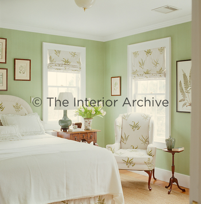A guest bedroom is a cool sanctuary of peppermint green and white, with a botanical theme using ferns as a motif for a set of framed prints and upholstery
