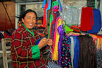 Tibetan woman knits accessories at her clothes stall on the Barkhor pilgrim circuit, Lhasa, Tibet.