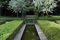 A round ivy-covered plant support is situated at one end of the pond creating a focal point for the bench behind