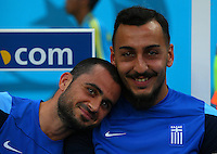 Loukas Vyntra of Greece jokes with team mate Konstantinos Mitroglou on the substitutes bench before kick off