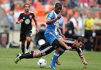 WASHINGTON, D.C. - AUGUST 19, 2012:  Chris Pontius (13) of DC United is knocked down by Michael Lahoud (13) of the Philadelphia Union during an MLS match at RFK Stadium, in Washington DC, on August 19. The game ended in a 1-1 tie.