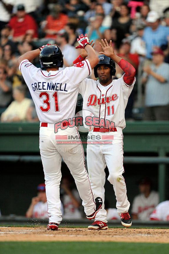 Right fielder Bo Greenwell (31) of the Greenville Drive is greeted by Alex Rijo (11) after hitting his second home run of the game against the Asheville Tourists on Wednesday, April 23, 2014, at Fluor Field at the West End in Greenville, South Carolina. (Tom Priddy/Four Seam Images)