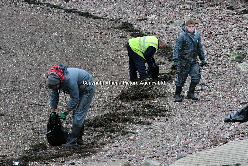 Pictured: Personnel works to contain an oil spill by a Valero jetty in Pembrokeshire, Wales, UK. Friday 04 January 2018<br /> Re: The Valero Jetty in Pembrokeshire, west Wales was closed off following a leak which had been contained.<br /> The Port of Milford Haven said a pollution control aircraft will carry out a survey.<br /> The firm Valero has apologised.