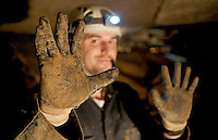 NWA Democrat-Gazette/DAVID GOTTSCHALK  Mud is caked on the gloves and clothes of Guy Schiavone, general manager and guide, Tuesday, October 11, 2016, after leading a tour on the Wild Tour of War Eagle Cavern on Beaver Lake. The Wild Tour gives visitors a guided realistic experience of spelunking that requires helmets, lights, gloves, knee pads and the willingness to get muddy and possibly wet.